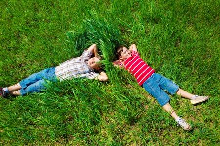 lying in grass: Dos ni�os so�ando en la hierba verde Foto de archivo
