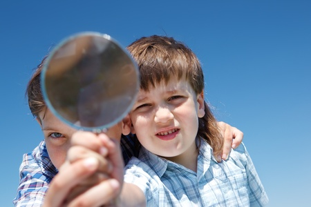 Kids exploring world with magnifier photo