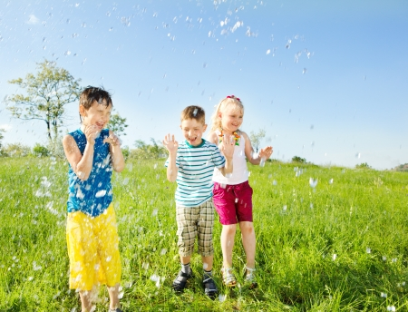 Laughing kids and  water drops falling on them photo