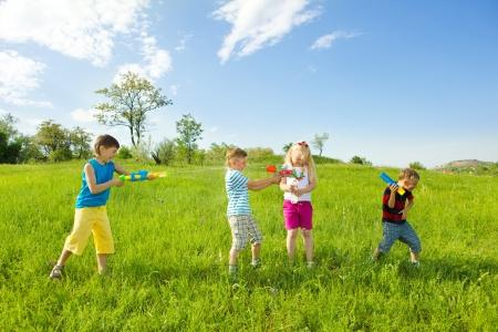 ni�os jugando en el parque: Los ni�os del agua de tiro el uno al otro