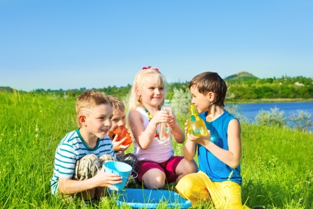 Little friends sit beside basin with containers for water Stock Photo - 13629999