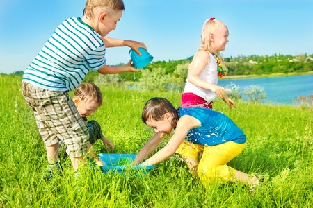 Cheerful preschoolers spreading water in the outdoors