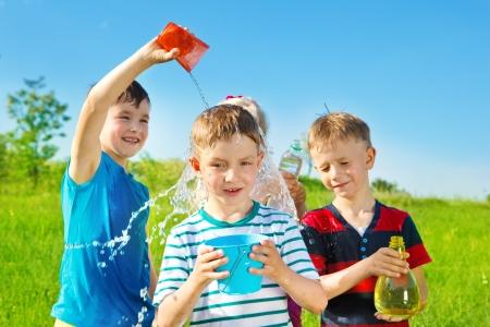 hermanos jugando: Los ni�os que juegan con el agua en el parque de verano