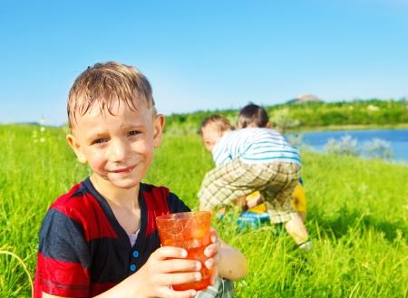 Smiling preschool boy holding water in glass photo