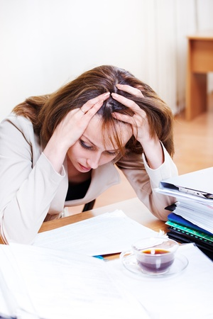Exhausted female reading papers at office photo