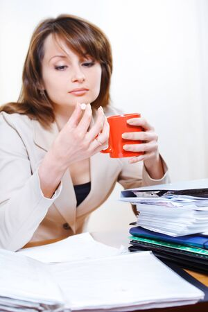 unhappy worker: Headache pill in hands of a tired young woman at work