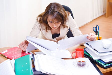 Tired young woman reading papers photo