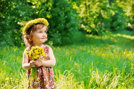 Sweet toddler girl with floral head wreath on and flowers bunch in hands photo