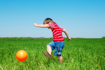 Elementary aged boy kicking ball in the field photo
