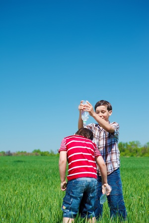 elementary age boys: Kid pouring water on his friend Stock Photo