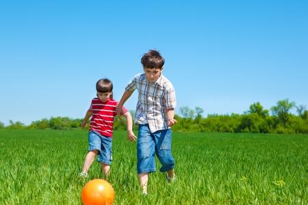 niños jugando en el parque: Niños jugando con la pelota en el campo Foto de archivo