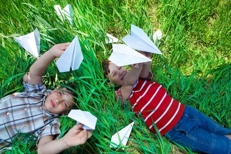 Kids lying on grass and playing with paper planes photo
