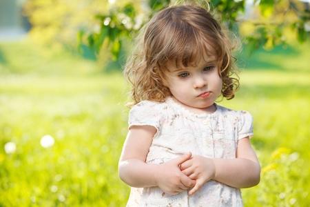Thoughtful curly girl in garden Foto de archivo