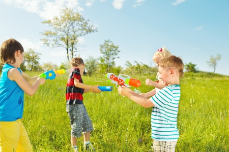 Kids group with water guns and soakers shooting  Foto de archivo