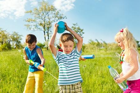hermanos jugando: Empapados de niños felices jugando con el agua en la pradera Foto de archivo