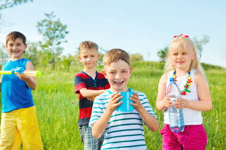 Kids group with toy water guns and other water containers  photo