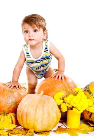 Portrait of a baby among ripe pumpkins photo
