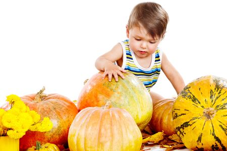 Lovely baby playing with large pumpkins photo