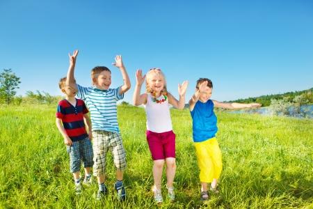 Opgewonden lachend kinderen groep op een zomerse dag Stockfoto