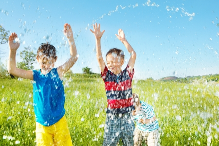 Happy children under water splashes Stock Photo