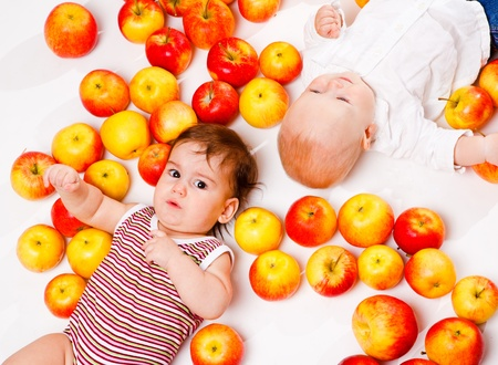 Portrait of two babies lying among ripe apples photo