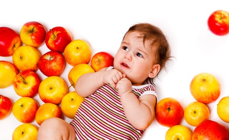 Sweet infant lying among yellow and red apples photo
