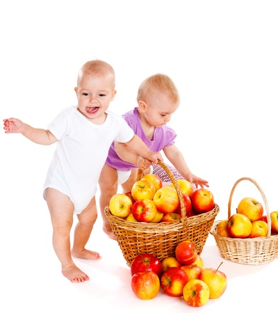 Two lovely babies playing with ripe apples photo