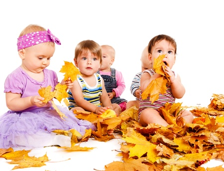 Group of babies playing with yellow leaves Foto de archivo