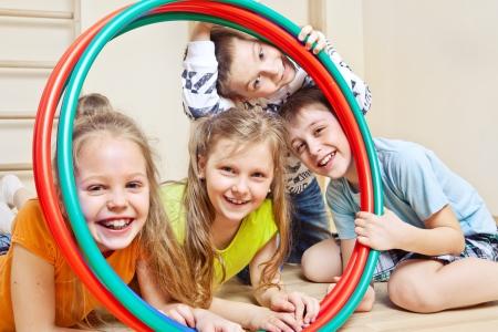 gymnastik: Lachende Kinder halten Hula-Hoops in einer Turnhalle