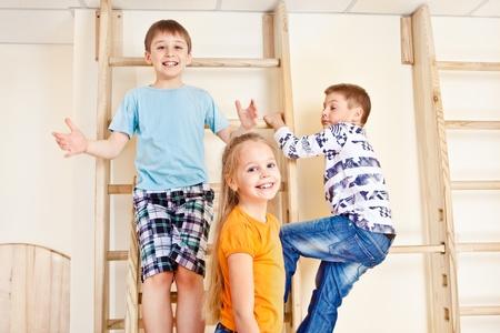 educacion fisica: Los niños se suben las barras de pared en un gimnasio de la escuela Foto de archivo