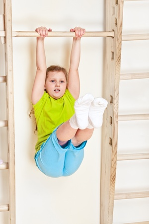 wall bars: Little girl lifting legs on the wall bars Stock Photo