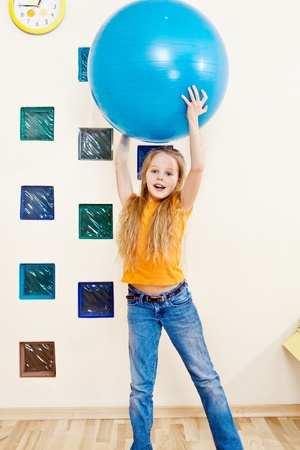 78: Sportive kid holding large gymnastic ball up high