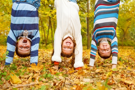 Three  kids upside down in autumn park Stock Photo
