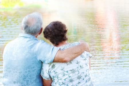 abuelos: Senior pareja sentada abrazándose y mirando el agua