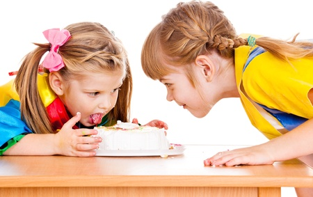 Sweet little girls eating a cake  photo