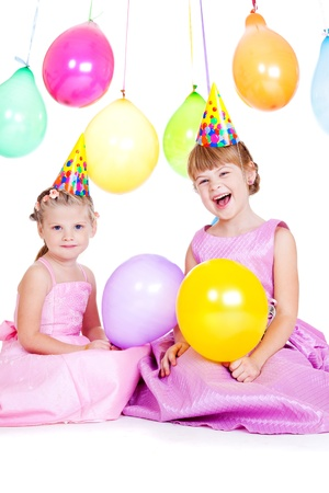 Laughing little girls in party hats holding balloons in hands photo