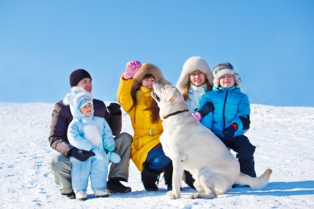 Winter family playing with Labrador Retriever  photo