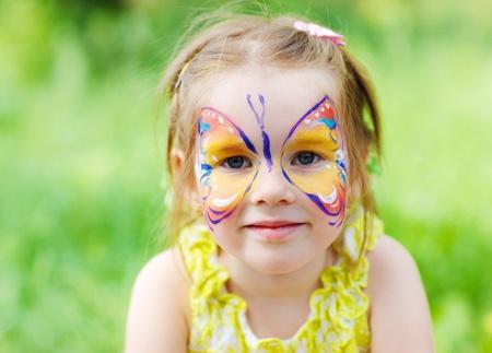 caritas pintadas: Diseño de la mariposa en la cara de una niña de edad preescolar Foto de archivo