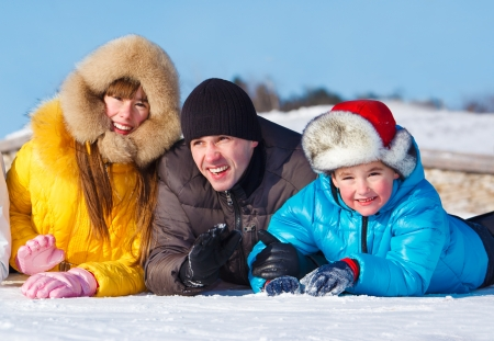 Children with father lie on snow photo