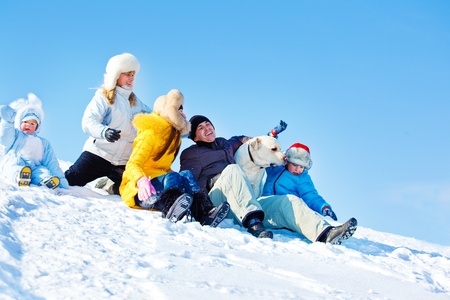 Laughing family and Labrador Retriever dog in winter park