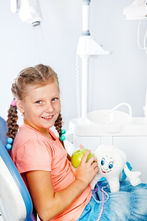 Cheerful kid with an apple at the dental clinic photo