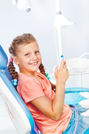 dental clinic: Cheerful kid with toothbrush and toothpaste at the dental clinic