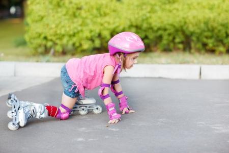 niño en patines: Niña en patines de ruedas levantarse para seguir adelante Foto de archivo