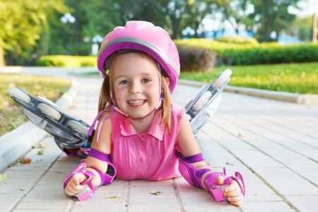 elbow pad: Cheerful preschool girl wearing inline roller skates and protective equipment Stock Photo