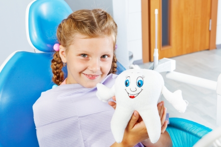 Cheerful child in dentist seat holding a toy tooth Foto de archivo