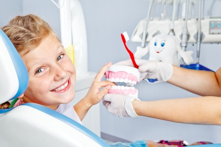 Happy child playing with toy dentures in dental office Stockfoto