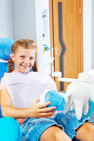 Smiling kid in a dentist chair with two soft tooth toys photo