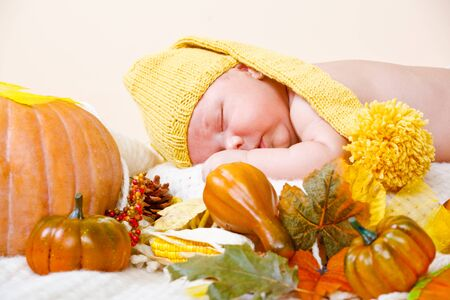 Baby in yellow hat sleeping beside pumpkin photo
