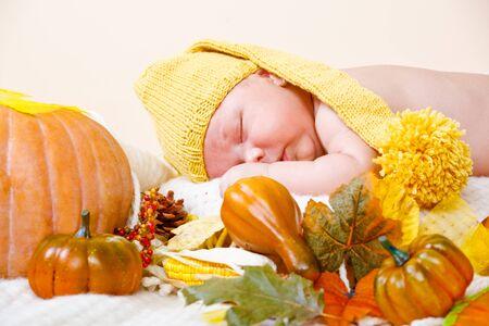 Baby in yellow hat sleeping beside pumpkin Stock Photo - 14630281
