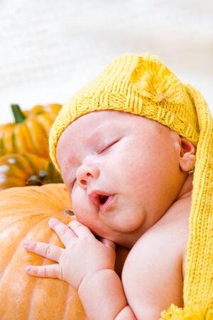 Sweet baby sleeping on pumpkin photo